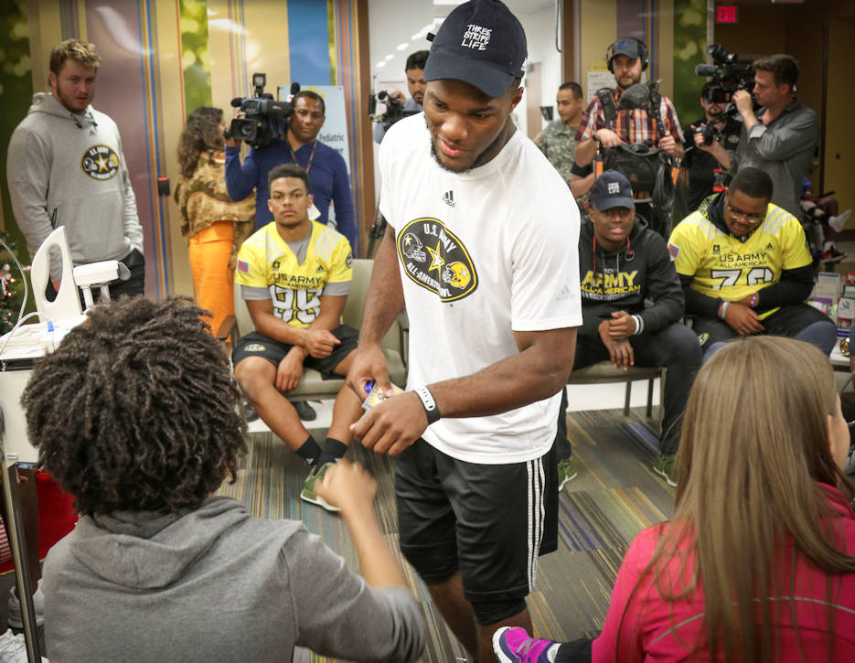 January 3, 2017 - Cam Akers, a running back from Clinton, Mississippi, who will represent the east team in the Army All-American Bowl on January 7, 2017 gives a fist bump to Brian McGraw, one of the children in the Children's Heath Department of the University Hospital in San Antonio, witnessed by fellow athletes. More than 30 athletes and their Soldier mentors took the opportunity to visit with kids at the hospital as part of a community relations event. For 16 years the Army All-American Bowl has been the nation's premier high school football game, serving as the preeminent launching pad for America's future college and National Football League stars. (U.S. Army Reserve Photo by Sgt. 1st Class Brent C. Powell)