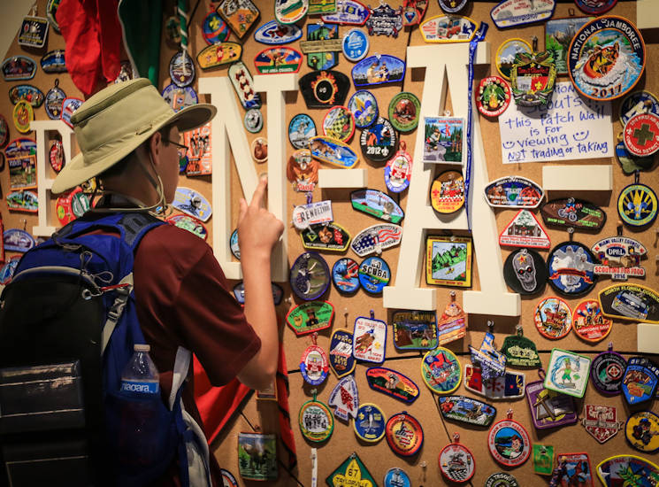 July 21, 2017 - A boy scout pins one of his patches to the Pin-a-Patch wall at the Summit Bechtel Reserve during the BSA 2017 National Jamboree near Glen Jean, West Virginia. The 2017 National Jamboree is being attended by 30,000 Boy Scouts, troop leaders, volunteers and professional staff members, as well as more than 15,000 visitors. Approximately 1,200 military members from the Department of Defense and the U.S. Coast Guard are providing logistical support for the event. (U.S. Army photo by Spc. Liem Huynh, 22nd Mobile Public Affairs Detachment)