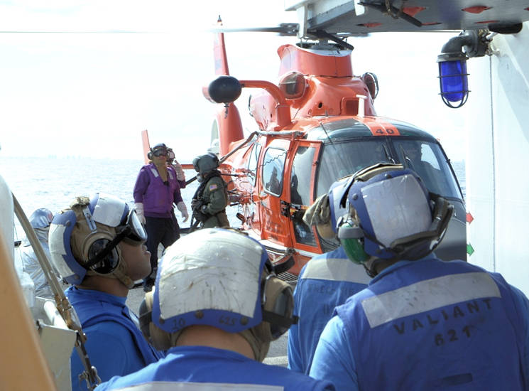 November 2016 - Coast Guard MH-65 Dolphin helicopter crewmember and Coast Guard Cutter Venturous fueling team members refuel the helicopter while the rotors are turning, executing a hot refueling evolution. Helicopter tiedown members observe the evolution for safety. (U.S. Coast Guard photo by Petty Officer 1st Class Richard Macaraeg)