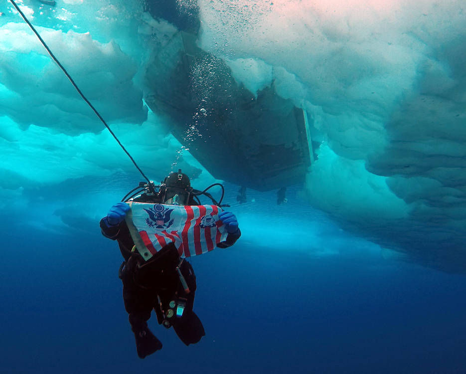 Coast Guard Petty Officer 2nd Class Adam Harris, a member of a joint Coast Guard-Navy dive team deployed on the Coast Guard Cutter Healy, holds a Coast Guard ensign during a cold water ice dive off a Healy small boat in the Arctic, July 29, 2017. The joint dive team successfully completed the first shipboard Coast Guard dive operations in the Arctic in eleven years. (U.S. Coast Guard photo by Petty Officer 1st Class David Bradbury)