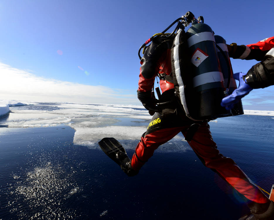 Coast Guard Petty Officer 1st Class Brendon Ballard enters the water from a Coast Guard Cutter Healy small boat during a cold water ice dive in the Arctic, July 30, 2017. Divers are the Coast Guard's primary resource for the service's subsurface capabilities and perform a full spectrum of Coast Guard missions; including underwater inspections and maintenance on icebreakers and other cutters, surveying critically endangered species habitats and providing underwater searching capabilities for search and rescue operations. (U.S. Coast Guard photo by Petty Officer 2nd Class Meredith Manning)