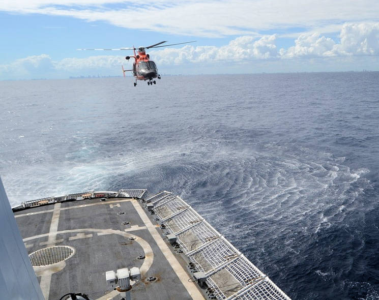 November 2016 - A Coast Guard MH-65 Dolphin helicopter crew conducts a landing approach to Coast Guard Cutter Venturous's flight deck with the Miami skyline in the background. (U.S. Coast Guard photo by Petty Officer 1st Class Richard Macaraeg)