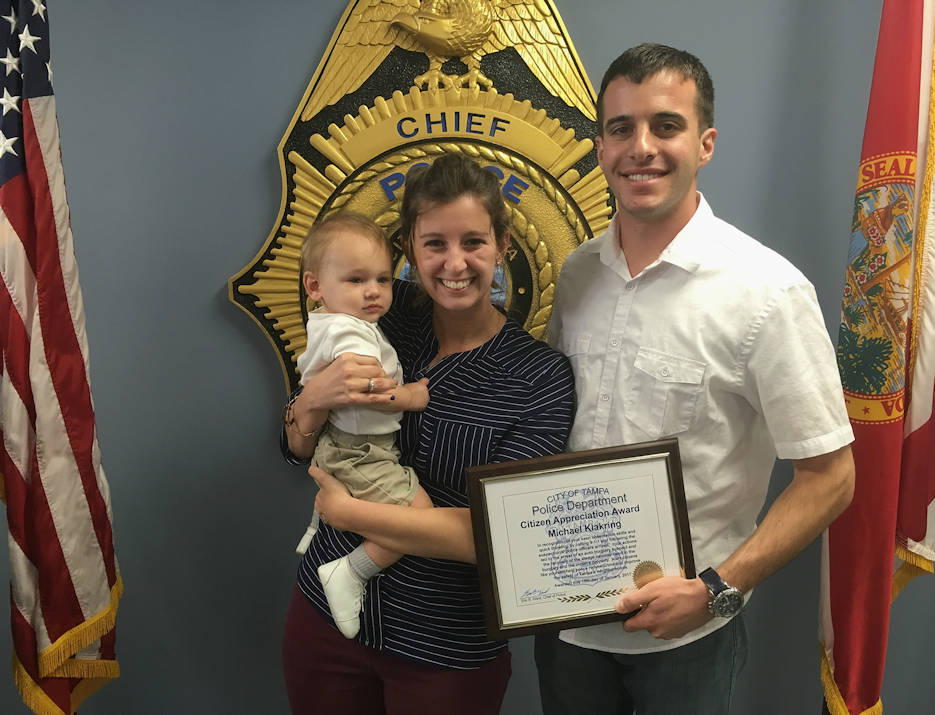 January 19, 2017 - Coast Guard Lt. Michael Klakring, an MH-60 Jayhawk helicopter pilot at Air Station Clearwater, Florida, stands with his wife, Brigette Klakring, and son, Luke Klakring, after receiving the Tampa Police Department's Citizen Appreciation Award at TPD headquarters in Tampa, Florida. Klakring received the award for helping apprehend a suspected car burglar in December 2016. (U.S. Coast Guard photo by Petty Officer 2nd Class Ashley J. Johnson)