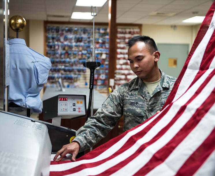 October 24, 2017 - Inside the Charles C. Carson Center, located at Dover Air Force Base in Dover, Del., Senior Airman John Paul Javier presses the United States National Flag for use during mortuary affairs operations. The Charles C. Carson Center is home to the Port Mortuary which is responsible for returning all Department of Defense service members, civilians, and contractors who perish during contingency operations overseas. The 73,000 square foot facility was built in 2003 at a cost of $30 million. (U.S. Army photo by Master Sgt. Brian Hamilton)