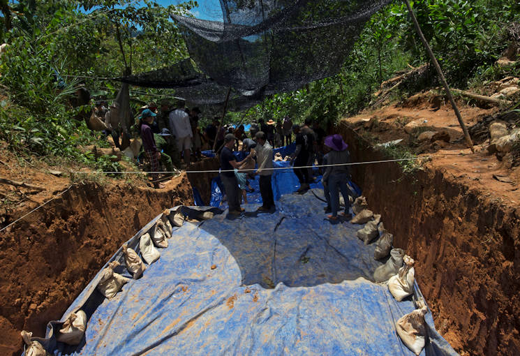 June 6, 2017 - U.S. service members work alongside Vietnamese personnel to place sandbags on the edge of a tarp to keep the soil inside of excavated units dry in Phuoc Son providence, Vietnam, June 6, 2016. The mission of DPAA is to provide the fullest possible accounting for our missing personnel to their families and their nation. (U.S. Air Force photo by Staff Sgt. David Owsianka)