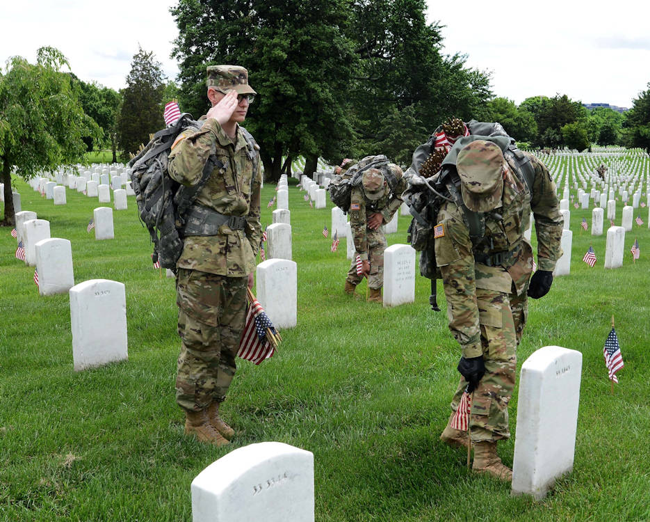 """U.S. Army Pvt. Gabriel Thyfault, left, renders honors while U.S. Army Spc. Nayib Pagan places an American flag in front of a headstone during """"Flags In'' at Arlington National Cemetery in Arlington, VA on May 25, 2017. Thyfault and Pagan are transportation specialists assigned to the 529th Regimental Support Company, 4th Battalion, 3rd U.S. Infantry Regiment, known as """"The Old Guard"""". (DoD photo by Sebastian J. Sciotti Jr.)"""