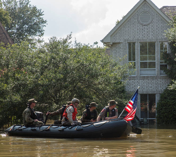 August 31, 2017 - Marines with Charlie Company, 4th Reconnaissance Battalion, 4th Marine Division, Marine Forces Reserve, along with a member of the Texas Highway Patrol and Texas State Guard, patrol past a flooded house in Houston, Texas, August 31, 2017. Hurricane Harvey landed August 25, 2017, flooding thousands of homes and displaced over 30,000 people. (U.S. Marine Corps photo by Lance Cpl. Niles Lee)