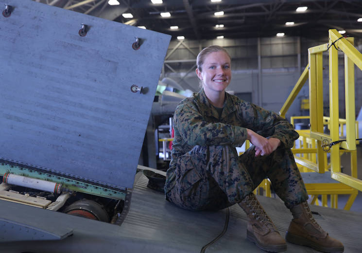 March 3, 2017 - Cpl. Callahan Brown sits atop an aircraft that's undergoing maintenance at Marine Aviation Logistics Squadron 26 on Marine Corps Air Station New River. Brown is currently a full time student at Coastal Carolina Community College and plans to commission to become an officer when she becomes a sergeant or completes her degree. Brown is the adjutant for MALS 26. (U.S. Marine Corps photo by Lance Cpl. Juan Madrigal)