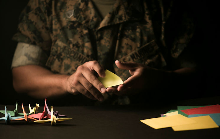 April 19, 2017 - Staff Sgt. Ismael Esconde, the substance abuse control officer with Headquarters and Service Company, 3rd Battalion, 3rd Marine Regiment, folds an origami crane with finished ones on the table next to him at building 267 aboard Marine Corps Base Hawaii. Esconde uses origami as a way to make a positive impact in his local community. (U.S. Marine Corps photo by Sgt. Brittney Vella)