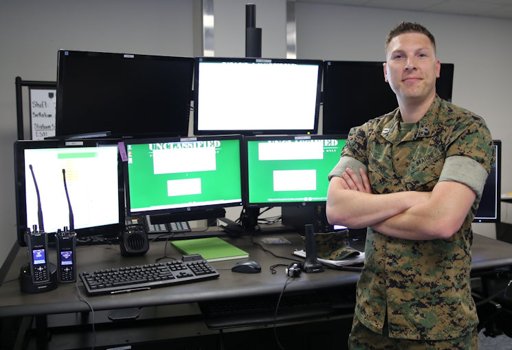 May 2, 2017 - U.S. Marine Corps Maj. Mark Simmons, systems engineer for Consolidated Emergency Response System, stands in front of a newly-installed CERS emergency dispatcher workstation aboard Marine Corps Base Quantico, VA. CERS aggregates multiple capabilities ... Enhanced 911, Computer-Aided Dispatch, and fire station alerting ... into a single workstation, giving emergency dispatchers the ability to quickly dispatch the appropriate assets where necessary. CERS increases the effectiveness of emergency response operations aboard Marine Corps installations worldwide. (U.S. Marine Corps photo by Ashley Calingo, MCSC)