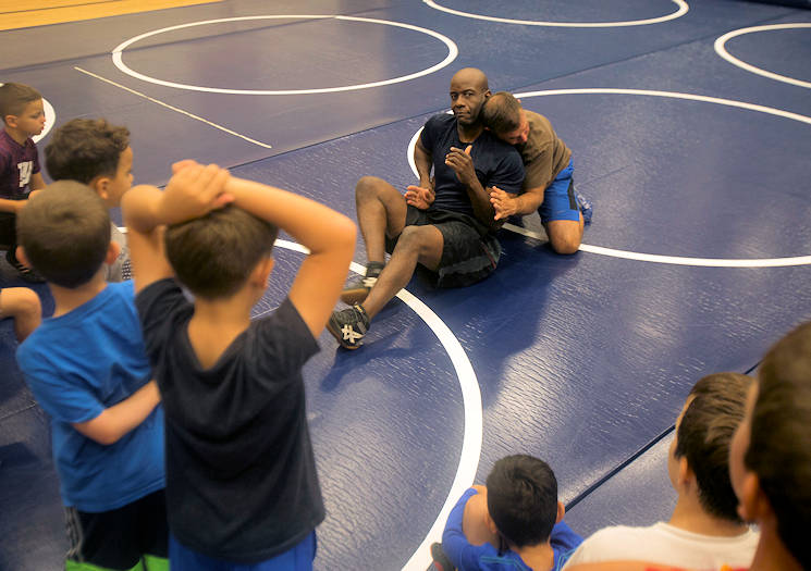 October 12, 2017 - Retired Master Gunnery Sgt. Gus Alexander, the head coach of Marine Corps Base Hawaii's youth wrestling team, leads wrestlers in warm-ups during a practice at the Youth Semper Fit Center. The program, organized by Marine Corps Community Services, works in conjunction with Police Activities League and USA Wrestling to arrange wrestling tournaments with competitors from across the island of Oahu. (U.S. Marine Corps photo by Lance Cpl. Luke Kuennen)
