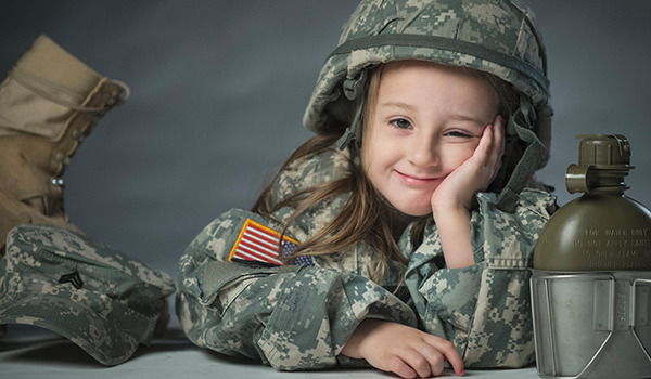 Lily, daughter of Army Sgt. James Newby, grins as she poses for portraits with her father's uniform items on Fort Meade, MD. (U.S. Air Force photo by Staff Sgt. Vernon Young Jr.)