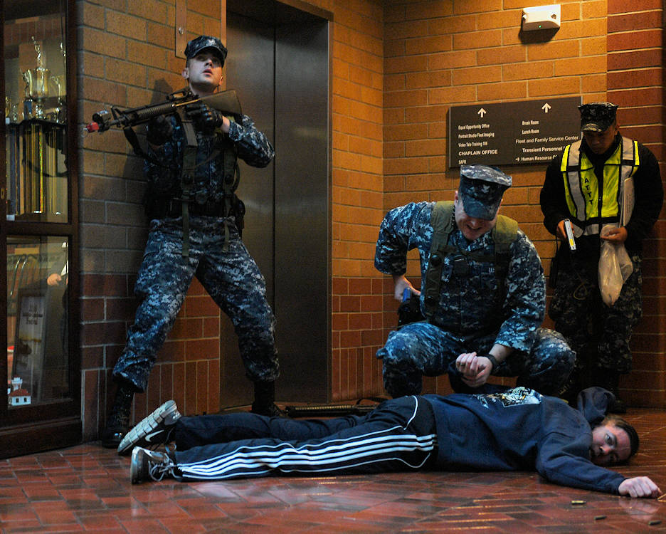 February 1, 2017 - U.S. Navy Master-at-Arms 2nd Class Nathan Bratton maintains lookout as U.S. Navy Master-at-Arms 2nd Class Tyler Allhouse restrains U.S. Navy Chief Master-at-Arms Ryan Lyhodges during an active shooter drill on Naval Station Everett. The drill was part of Solid Curtain-Citadel Shield, an annual exercise using realistic scenarios to ensure Navy Security Forces maintain a high level of readiness and are capable of responding to dynamic threats. (U.S. Navy photo by Mass Communication Specialist 2nd Class Alex Van'tLeven)