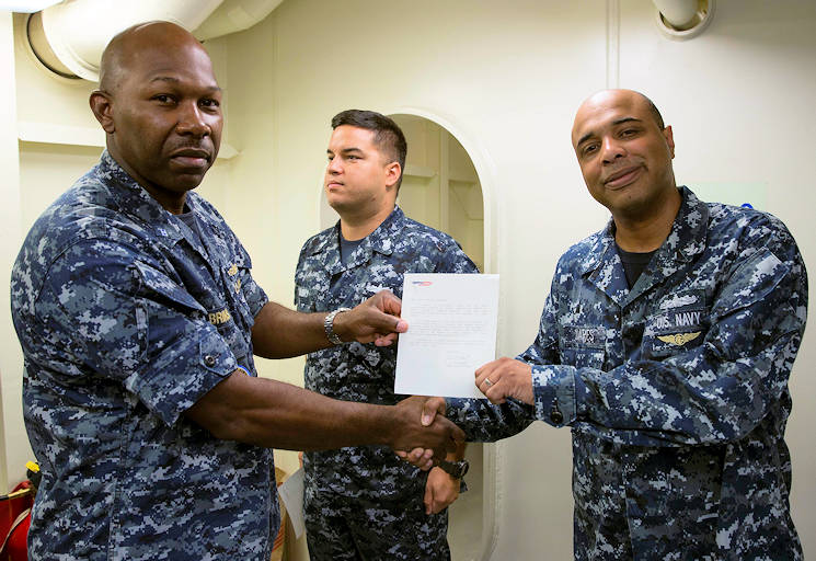 August 15, 2016 - Interior Communications Electrician 2nd Class Henrique Soares, assigned to Pre-Commissioning Unit Gerald R. Ford (CVN 78), is presented a letter of appreciation from the commanding officer by Chief Warrant Officer Ernest Brinson. Soares received the letter for his work during Ford's change of command ceremony in April 2016. (U.S. Navy photo by Mass Communication Specialist Seaman Apprentice Gitte Schirrmacher)