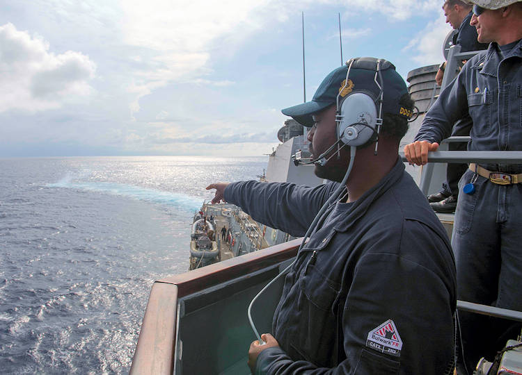 Navy Seaman Dorsey Cadette assigned to the guided-missile destroyer USS Stethem, points out a smoke signal during man-overboard training while conducting routine operations in the South China Sea, July 10, 2017. Stethem was on patrol in the South China Sea supporting security and stability in the Indo- Pacific region. (U.S. Navy photo by Petty Officer 2nd Class Ryan Harper)