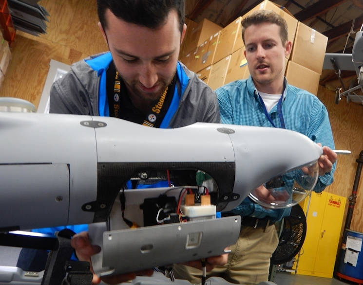 June 2017 - Navy scientist Jordan Lieberman, left, works with engineer Jonathan Crook to install the SCAPEGOAT payload onto a Boeing Insitu Scan Eagle unmanned aerial vehicle (UAV) prior to a system test flight. The SCAPEGOAT system - which includes modular interfaces to multiple chemical, biological, and radiological sensors and UAV platforms - was developed by junior scientists and engineers engaged in the Naval Surface Warfare Center Dahlgren Division sponsored Sly Fox Program over a six-month period. (U.S. Navy photo by Stacia Courtney)