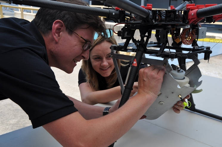 June 2017 - Navy scientist Charles Miller and mathematician Jessica Hildebrand perform pre-flight checks on the SCAPEGOAT chemical, biological, and radiological (CBR) detection system. The SCAPEGOAT system - developed by a team of Naval Surface Warfare Center Dahlgren Division junior scientists and engineers - demonstrates the capability to deploy a modular CBR sensor system aboard multiple unmanned aerial vehicle platforms. (U.S. Navy photo by John Joyce)