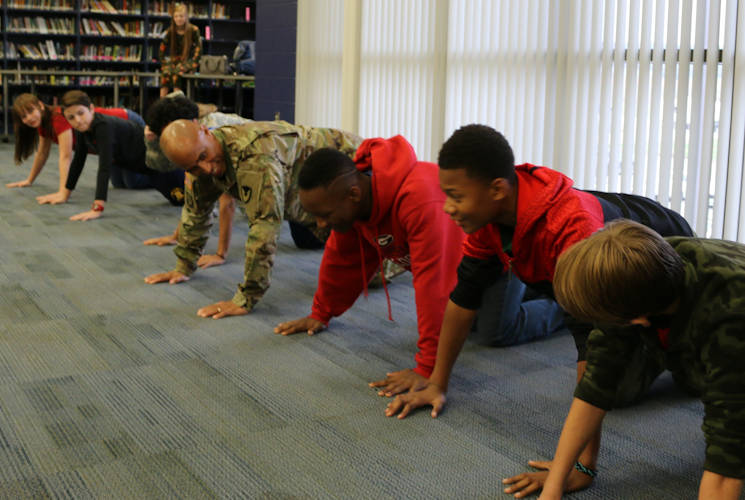 November 8, 2017 - Sgt. Maj. Jon Martin takes on a pushup competition with seventh and eighth grade students at Buckhorn Middle School. Martin and eight other AMCOM Soldiers shared their message of military service with the seventh and eighth graders at the school. (U.S. Army photo by Kari Hawkins, Aviation & Missile Command)