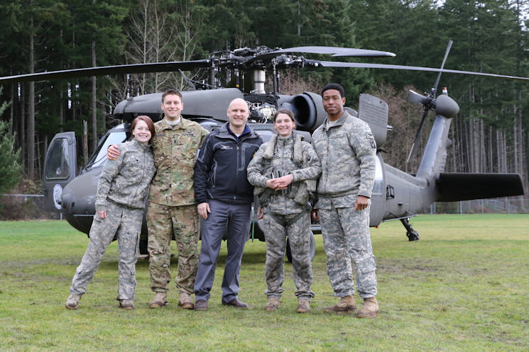 December 13, 2016 - Specialist Melissa Marsolek, 1st Lt. Scott Darragh, Specialist Keely Killebrew, and Chief Warrant Officer 2 Sean Quillin, all from Charlie Company, 1st Battalion, 140th Aviation Regiment, with Jeff Coleman (center), aviation instructor at Emerald Ridge High School, Puyallup, Washington in front of their UH-60 Black Hawk helicopter. The visit to the high school was part of a partnership with the school's aviation program which gives aspiring pilots the chance to talk to real pilots and sit in real helicopters. (Courtesy photo by Jennifer Picardo)