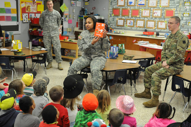 March 2, 2017 - Sergeant 1st Class Arianna Joe, center, a chaplain's assistant with the 88th Regional Support Command, introduces Dr. Seuss' Green Eggs and Ham before reading it to a group of Kindergarten students at Lawrence-Lawson Elementary School in Sparta, Wisconsin, as part of Read Across America. Staff Sgt. Nicholas Gimson, left, and Sgt. Robert Clark, both with the 88th Regional Support Command, also read to other students at the elementary school. (U.S. Army photo by Zachary Mott)
