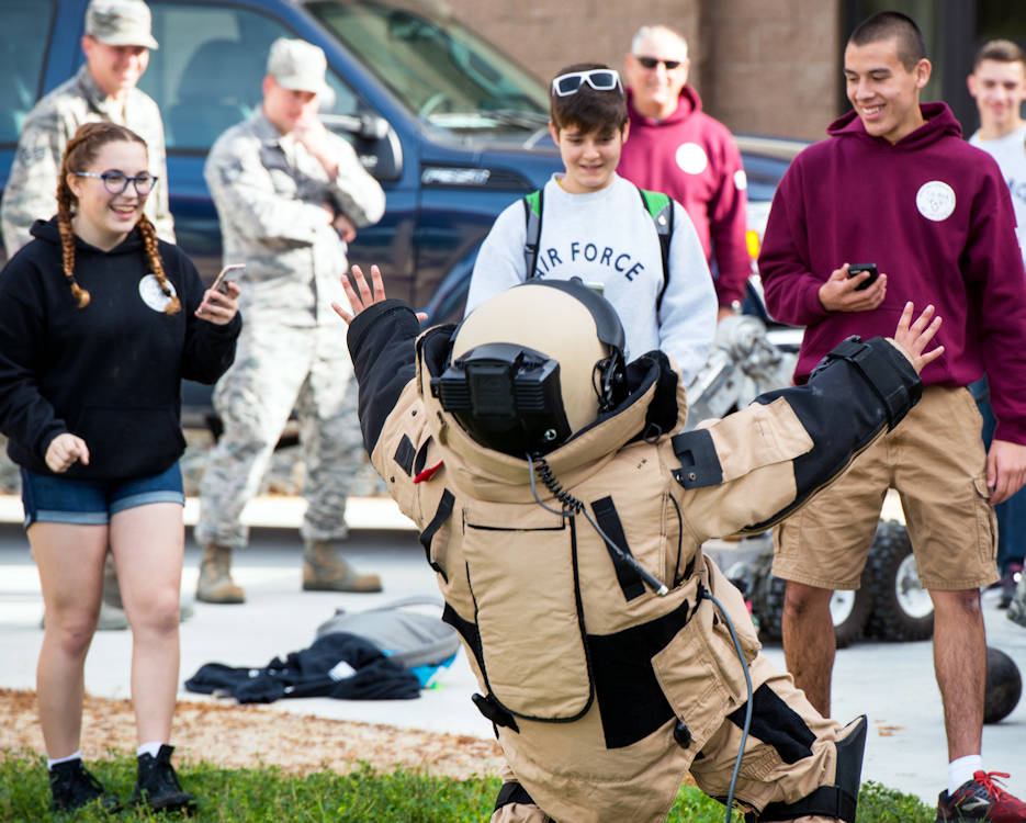 March 16, 2017 - A student from Whitney High School, Rocklin, Calif., falls backwards from the weight of the Explosive Ordnance Disposal 9 suit during Travis Tour Day. Students toured several aircraft, air traffic control tower, dormitories and had the opportunity to talk with Travis Air Force Base personnel about military life. The purpose of the tour is to support Air Force recruiting by inspiring patriotism and encouraging young men and woman to serve in the military. (U.S. Air Force photo by Louis Briscese)