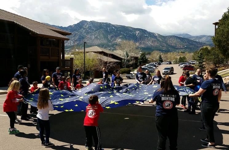April 2, 2017 - Attendees participate in a parachute activity during a Tragedy Assistance Program for Survivors Good Grief Camps event at Cheyenne Mountain Resort, Colorado Springs, Colorado. The activity provided play therapy for children who had lost military family members. (Air Force photo by Senior Airman Arielle Vasquez)
