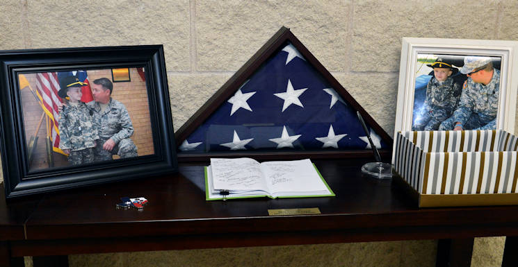 January 24, 2017 - A folded American flag with photos of  honorary Texas Army National Guard Spc. Rowan Jameson Windham (10) with fellow soldiers are displayed at Windham's final roll call ceremony conducted by the Texas Military Department at Camp Mabry in Austin, Texas. The roll call serves as a memorial ceremony to represent the permanent loss of a soldier. Windham spent the majority of his 10 years battling a rare genetic disorder called Shwachman-Diomand syndrome. (U.S. Army National Guard photo by Sgt. Elizabeth Pena)
