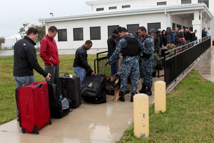 January 29, 2017 - Petty Officer 3rd Class Gerardo Martinez and his explosives detecting canine, K-OS, inspect luggage at the notional Conch Republic border as part of Operation Warrior Anvil. Security Office personnel from U.S. Naval Air Station Key West participated in Operation Warrior Anvil, a validation exercise held in Key West, Florida, by 7th Military Information Support Battalion, 4th Military Information Support Group. The exercise validated teams through unparalleled training with joint, inter-agency, and civic partners in real-world urban environments that reinforced psychological operations fundamentals, fostered teamwork, and strengthened character.(U.S. Army photo by Capt. Stephen Von Jett)