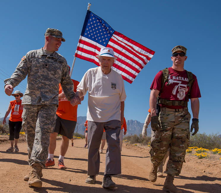 March 19, 2017 - Retired U.S. Army Col. Ben Skardon, 99, a survivor of the Bataan Death March, walks in the annual Bataan Memorial Death March at White Sands Missile Range, accompanied by green-to-gold New Mexico State University Army Reserve Officers' Training Corps cadet Ryan Bradley (left) and Spc. Michael Cole of the McAfee Army Health Clinic - both Army medics. This was the tenth time Skardon walked a distance of eight and a half miles in the march - and he is the only survivor who walks in it. (U.S. Army Reserve photo by Staff Sgt. Ken Scar)