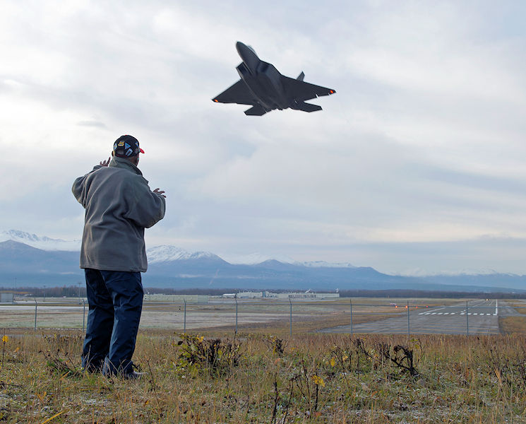 Army Air Corps Staff Sgt. Leslie Edwards, a Tuskegee Airman of the 617th Bombardment Squadron, stands on a mound overlooking the flightline as an F-22 Raptor of the 477th Fighter Group soars past at Joint Base Elmendorf-Richardson, Alaska, Oct. 14, 2017. The 617th Bombardment Squadron was one of four Tuskegee Airmen bomber squadrons during World War II that made up the 477th Bombardment Group. In 2007, the 477th Bombardment Group became the 477th Fighter Group, bringing with it the legacy of Tuskegee airmen to Alaska. (U.S. Air Force photo by Senior Airman Javier Alvarez)
