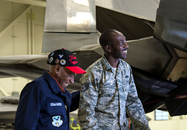 U.S. Army Air Corps Staff Sgt. Leslie Edwards, a Tuskegee Airman of the 617th Bombardment Squadron, shares a moment with U.S. Air Force Staff Sgt. Stephen Teamer, 477th Aircraft Maintenance Squadron crew chief, at Joint Base Elmendorf-Richardson, Alaska, Oct. 14, 2017. The 617th Bombardment Squadron was one of the four Tuskegee Airmen bomber squadrons during World War II that made up the 477th Bombardment Group. In 2007, the 477th Bombardment Group became the 477th Fighter Group, bringing with it the legacy of Tuskegee Airmen to Alaska. (U.S. Air Force photo by Senior Airman Curt Beach)
