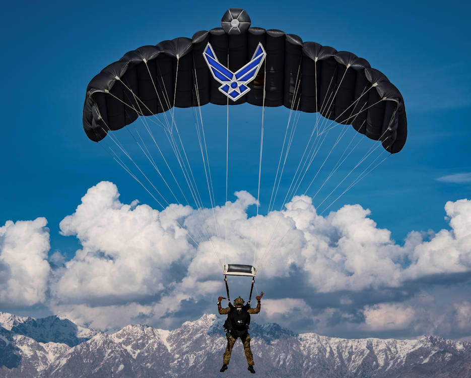 March 4, 2018 - A U.S. Air Force pararescueman assigned to the 83rd Expeditionary Rescue Squadron, Bagram Airfield, Afghanistan, operates the canopy of his parachute while conducting a high altitude, high opening military free fall jump with a panoramic view of snow covered mountains in Afghanistan. He jumped from a C-130J Super Hercules flown by the 774th Expeditionary Airlift Squadron, Bagram Airfield, Afghanistan. The pararescueman and his fellow Guardian Angel Team members conduct training on all aspects of combat, medical procedures and search and rescue tactics to hone their skills, providing the highest level of tactical capabilities to combatant commanders. (Image created by USA Patriotism! from U.S. Air Force photo by Tech. Sgt. Gregory Brook)