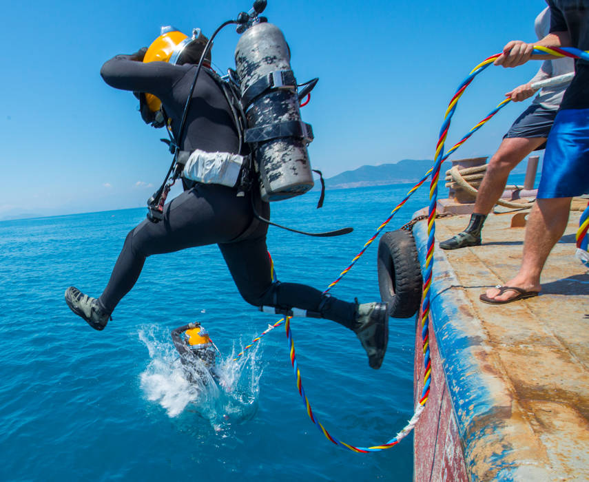 A pair of U.S. Army divers from the 7th Engineer Dive Detachment jump into the water during an underwater recovery mission near Nha Trang, Vietnam, March 20, 2018. Divers plunged 80 feet to the sea floor and spent about an hour dredging sediment, which was then screened for human remains and material evidence that could lead to the identification of missing American service members. ( U.S. Army photo by Sean Kimmons)