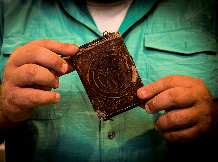 Former U.S. Army Sgt. Tony Fantasia displays the wallet that he attributes saving his life at his shop in San Antonio, Texas on June 29, 2018. Working with leather has aided Fantasia's battle with PTSD that he developed after his deployments to Southwest Asia as a medic. He now runs an outreach program for veterans focusing on various artistic outlets. (U.S. Air Force photo by Senior Airman Keifer Bowes)