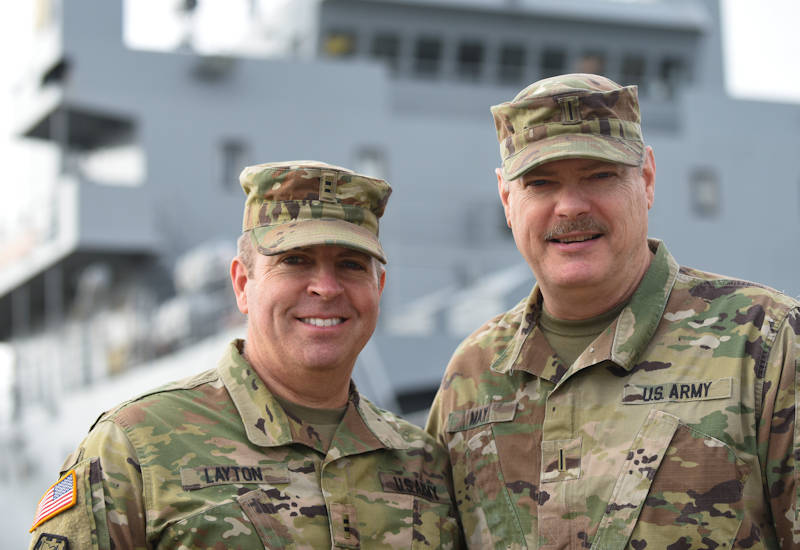 Left, U.S. Army Chief Warrant Officer 2 Nathaniel Layton, 97th Transportation Company, 7th Transportation Brigade (Expeditionary) chief engineer, and Chief Warrant Officer 5 Patrick May, Office of the Chief of Transportation chief maritime qualification director, pose for a photo near a Logistics Support Vessel docked at Third Port at Joint Base Langley-Eustis, VA on January 11, 2018. Layton and May, cousins, reconnected after being stationed together at Fort Eustis. (U.S. Air Force photo by Senior Airman Kaylee Dubois)