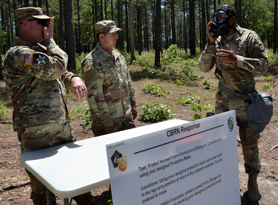 Army Cyber Protection Brigade Soldiers acting as trainers and evaluators demonstrate putting on a chemical protective mask for their CPB colleagues during warrior skills training at the CPB Cyber Stakes exercise at Fort Gordon, Ga., May 3, 2018. Cyber Stakes, the brigade's flagship biannual training event, provides CPB Soldiers and civilian employees with three days of instruction, collaboration and evaluation of core cyber, followed by two days of training and testing on basic Army warrior tasks for brigade troops. (U.S. Army photo by William Roche)