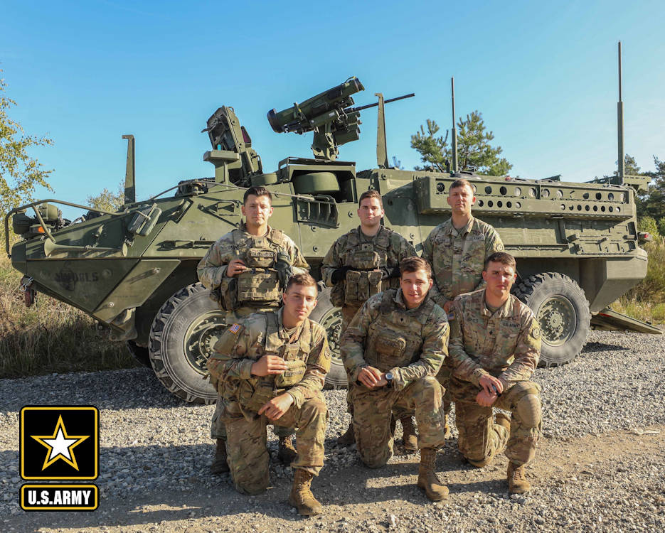 October 4, 2018 - Spc. Phillip Jones, Sgt. Kyle Clarke, Spc. Kyle Braun, Spc. Dominick Bass, Pfc. Logan Boeckmann and Spc. Nicholas Castaneda, assigned to U.S. Army 2nd Squadron, 2d Cavlary Regiment, who are members of the Common Remotely Operated Weapon Station - Javelin crew teams working as drivers and vehicle commanders, proudly pose in front of Stryker mounted javelin weapon system after conducting a CROWS-J live fire at the Grafenwoehr Training Area, Germany. (Image created by USA Patriotism! from U.S. Army photo by 1st Lt. Ellen C. Brabo, 2d Cavalry Regiment)