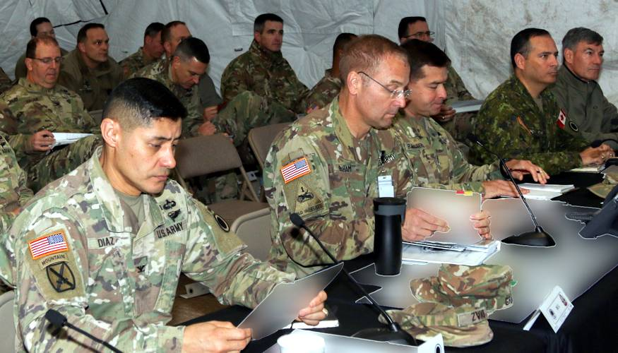 From front left to right, I Corps Chief of Staff Colonel Mario Diaz, I Corps Deputy Commanding General William Graham, I Corps Operations Sgt. Maj. Victor Ballesteros, Deputy Commanding General -Operations Michel-Henri St-Louis, receive a brief on the current status of the battle simulation during Warfighter Exercise 19-1, a tactical command post exercise that was held from October 2-10, 2018 on Joint Base Lewis-McChord that included units from across America's First Corps and attached components from the Army National Guard. This exercise gave the units the opportunity to hone their skills and test their capabilities through simulated battle drills. (U.S Army photo by Sgt. William Brown has been altered for security purposes by blurring classified materials.)