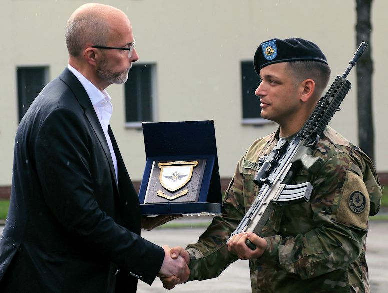 Mr. Jonathan Knott (left), Her Majesty's Ambassador to Poland shakes hands with Spc. Timothy Smith (right), a cavalry scout with Quickstrike Troop, 1st Squadron, 2nd Cavalry Regiment for achieving top graduate during a Potential Noncommissioned Officer Cadre Course ceremony on August 3, 2018 at Bemowo Piskie Training Area, Poland. Smith achieved top graduate and became the first U.S. Soldier to achieve it. The two-week long course focused on command principles and comprised of the practical application of these principles during a mixture of classroom instructions and infantry field exercises designed to develop leadership qualities of Soldiers. 2nd Cav. Regt. is on a six-month rotational assignment in support of the multinational battle group which comprises of U.S., U.K., Croatian and Romanian Soldiers who serve with the Polish 15th Mechanized Brigade as a defense and deterrence force in northeast Poland in support of NATO's Enhanced Forward Presence at BPTA. (U.S. Army photo by Sgt. John Onuoha)