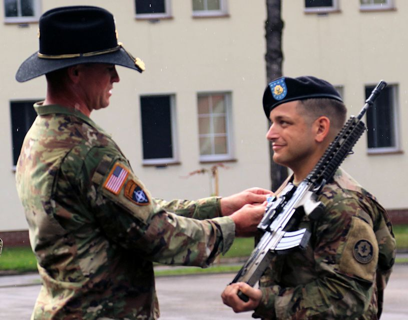 Ltc. Col. Timothy Wright (left), the commander of the 1st Squadron, 2nd Cavalry Regiment awards an Army Achievement Medal to Spc. Timothy Smith (right), a cavalry scout with Quickstrike Troop, 1st Squadron, 2nd Cav. Regt. for achieving top graduate during a Potential Noncommissioned Officer Cadre Course ceremony on August 3, 2018 at Bemowo Piskie Training Area, Poland. Smith achieved top graduate and became the first U.S. Soldier to achieve it. Adding to Spc. Timothy Smith's celebration, Ltc. Col. Timothy Wright recommended him to go to Ranger School as a reward for his achievement. (U.S. Army photo by Sgt. John Onuoha)