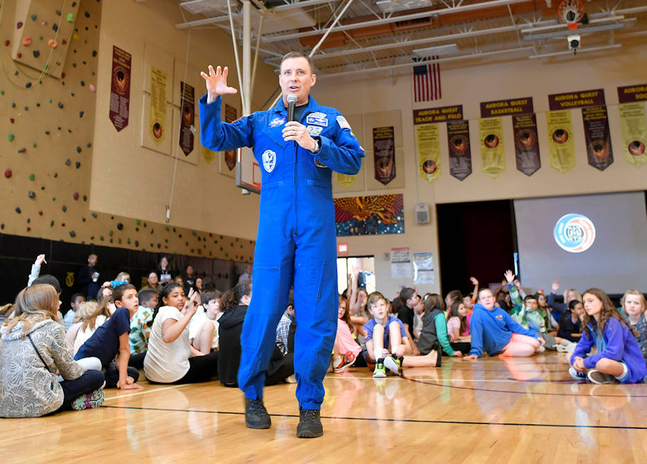 """Col. Jack """"2 Fish"""" Fischer, NASA astronaut, answers questions about his experiences in space posed by students during a general assembly on May 22, 2018 at Aurora Quest K-8 School, Aurora, Colorado. Fischer was invited as special guest and was a surprise to the nearly 600 students in attendance. (U.S. Air Force photo by Senior Airman Madison J. Ratley)"""
