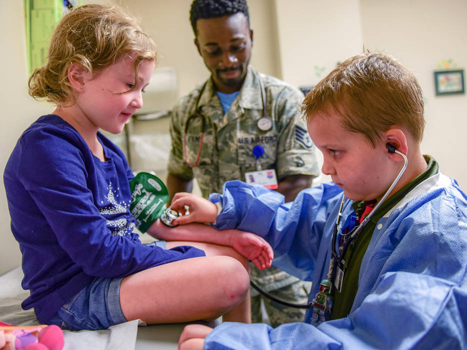 July 20, 2018 - Cancer survivor and airman for the day Caleb Pettit, 9, checks a patient's heartbeat while shadowing Air Force Capt. Charles Hutchings at Joint Base Charleston, South Carolina. (U.S. Air Force photo by Senior Airman Christian Sullivan)