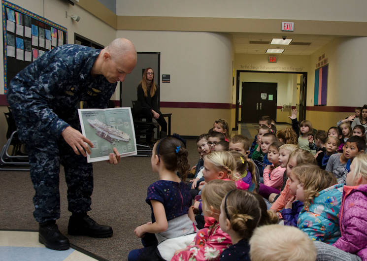 November 21, 2017 - Capt. Jeff Farah, commanding officer of the submarine tender USS Frank Cable (AS 40), shows a photo of the Frank Cable to students from Captain Strong Primary School in Battle Ground, Wash., Nov. 21. Frank Cable, currently in Portland, Ore. for a scheduled dry-dock phase maintenance avai lability, conducts maintenance and support of submarines and surface vessels in the Indo-Asia-Pacific region. (U.S. Navy photo by Mass Communication Specialist Heather C. Wamsley)