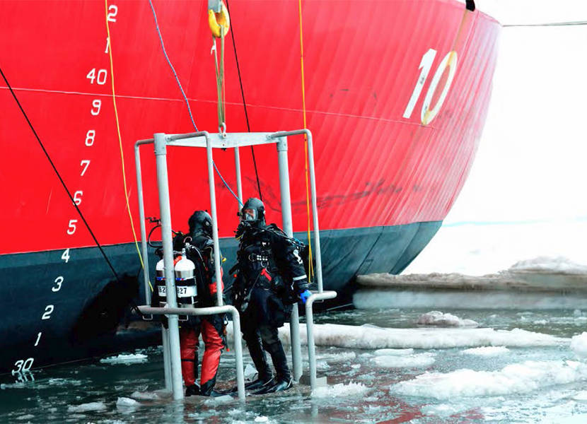 A U.S. Coast Guard Cutter Polar Star crew member lowers an underwater camera through Antarctic ice to help inspect the cutter for damage. (U.S. Coast Guard photo by Chief Petty Officer Nick Ameen)