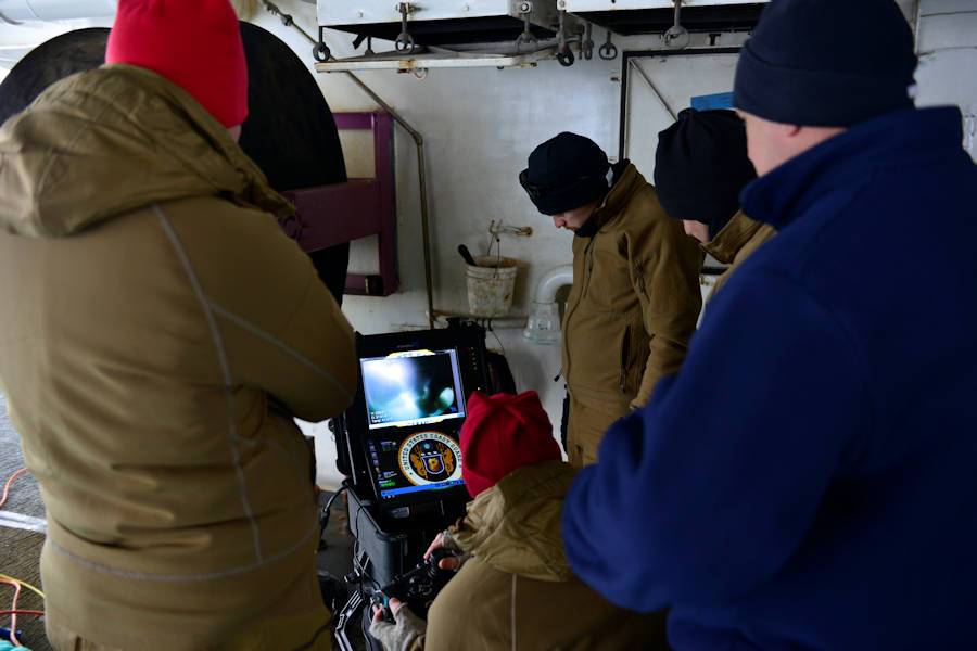 U.S. Coast Guard Cutter Polar Star and dive team watch camera feed from a diver inspecting the cutter. (U.S. Coast Guard photo by Chief Petty Officer Nick Ameen)