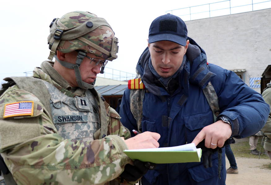 Army Capt. Timothy Swanson, a communications support officer with the 407th Civil Affairs Battalion, engages a citizen of fictional town Kittensee, during a civilians on the battlefield scenario, in the Hohenfels Training Area on Dec. 9, 2018 in Hohenfels, Germany. The battlefield scenario is associated with Combined Resolve XI that is a biannual exercise that serves as the combat training center certification exercise for regionally allocated forces. This iteration of the exercise takes place in two phases at the Grafenwoehr and Hohenfels training areas between Nov. 26 - Dec. 14, 2018 and Jan. 13 - 25, 2019. (U.S. Army photo by Sgt. Kevin Valentine)