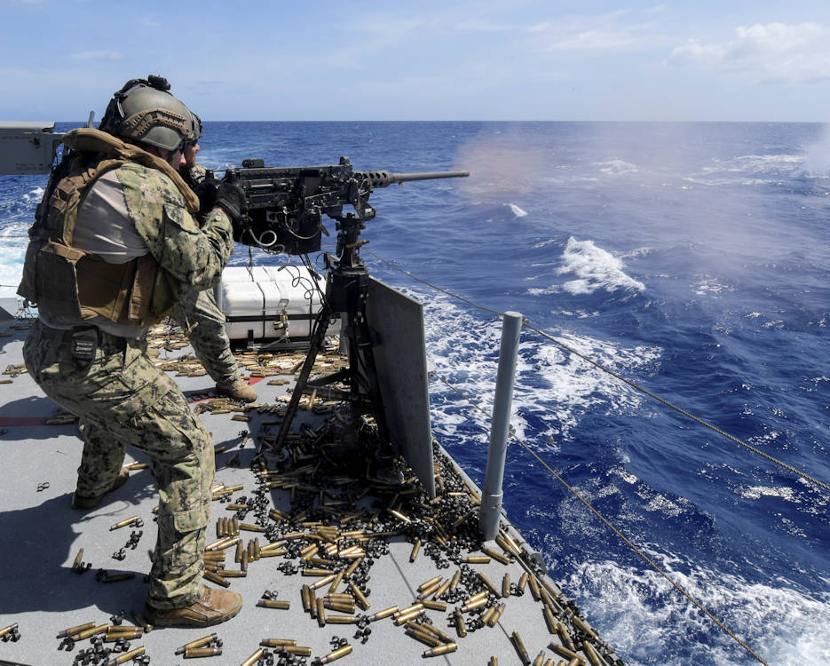 Gunner's Mate 2nd Class Michael DeCesare, assigned to Coastal Riverine Squadron (CRS) 4, Det. Guam, fires an M2 machine gun aboard a Mark VI patrol boat during a crew-served weapons qualification in the Philippine Sea, April 12, 2018. CRS-4, Det. Guam, assigned to Costal Riverine Group 1, Det. Guam, is capable of conducting maritime security operations across the full spectrum of naval, joint and combined operations. Further, it provides additional capabilities of port security, embarked security, and theater security cooperation around the U.S. 7th Fleet area of operations. (U.S. Navy Combat Camera photo by Mass Communication Specialist 1st Class Cory Asato)