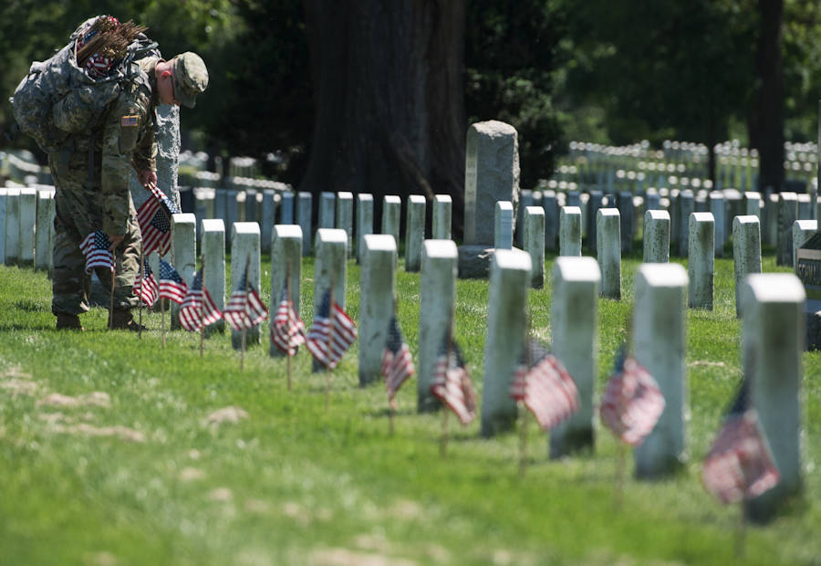 """A soldier assigned to the 3d U.S. Infantry Regiment (The Old Guard), places flags at headstones during """"Flags In"""" at Arlington National Cemetery in Arlington, Virginia on May 24, 2018. Soldiers from the Old Guard have honored our nation's fallen heroes by placing U.S. flags at gravesites for service members buried at both Arlington National Cemetery and the U.S. Soldiers' and Airmen's Home National Cemetery just prior to the Memorial Day weekend. Within four hours, more than 1,000 Soldiers placed 234,537 flags in front of every headstone and Columbarium and niche wall column. (U.S. Army photo by Spc. Lane Hiser)"""