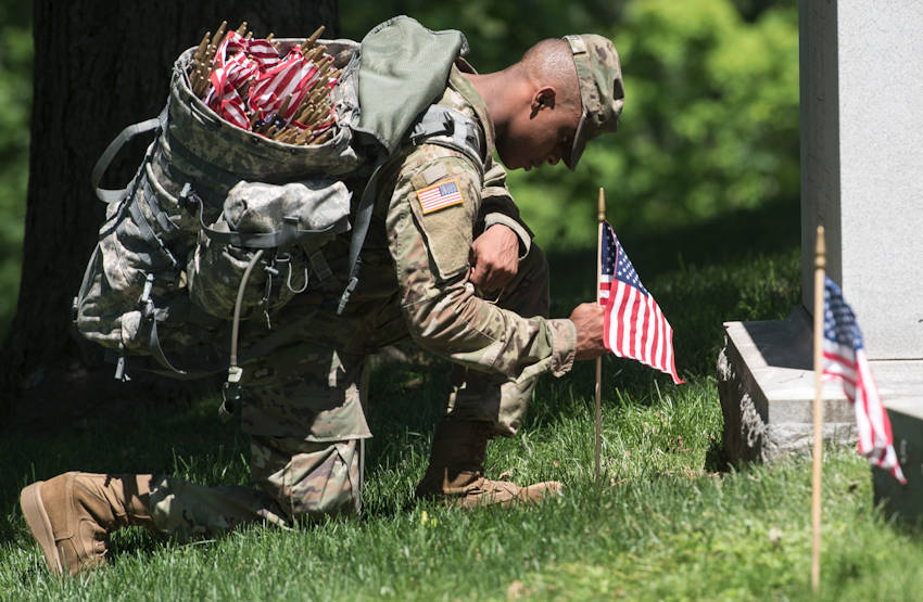 """A soldier assigned to the 3d U.S. Infantry Regiment (The Old Guard), takes a respectful knee as he places a flag at headstones during """"Flags In"""" at Arlington National Cemetery in Arlington, Virginia on May 24, 2018. Soldiers from the Old Guard have honored our nation's fallen heroes by placing U.S. flags at gravesites for service members buried at both Arlington National Cemetery and the U.S. Soldiers' and Airmen's Home National Cemetery just prior to the Memorial Day weekend. Within four hours, more than 1,000 Soldiers placed 234,537 flags in front of every headstone and Columbarium and niche wall column. (U.S. Army photo by Spc. Lane Hiser)"""