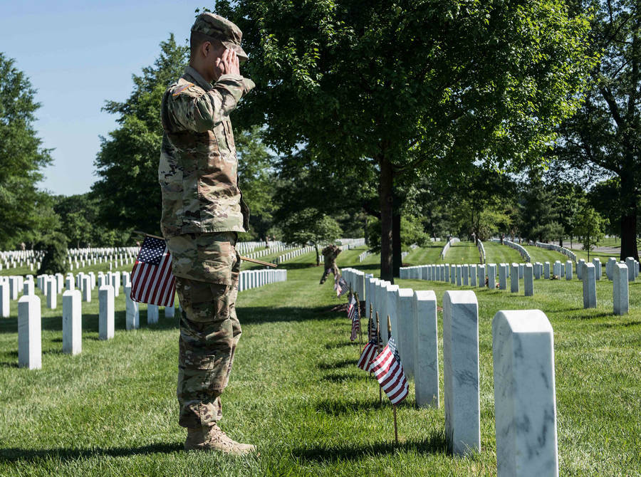 """A soldier assigned to the 3d U.S. Infantry Regiment (The Old Guard), salutes a headstone after placing a flag at it during """"Flags In"""" at Arlington National Cemetery in Arlington, Virginia on May 24, 2018. Soldiers from the Old Guard have honored our nation's fallen heroes by placing U.S. flags at gravesites for service members buried at both Arlington National Cemetery and the U.S. Soldiers' and Airmen's Home National Cemetery just prior to the Memorial Day weekend. Within four hours, more than 1,000 Soldiers placed 234,537 flags in front of every headstone and Columbarium and niche wall column. (U.S. Army photo by Spc. Gabriel Silva)"""